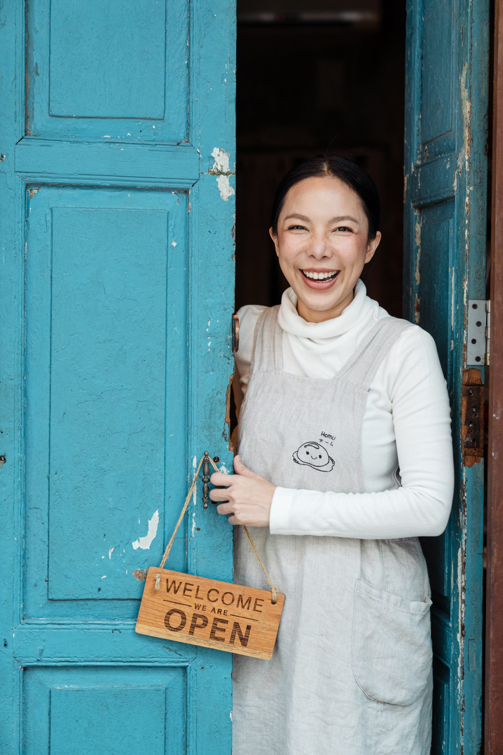 Happy ethnic woman in apron standing at entrance of own cafe door, holding WELCOME WE ARE OPEN sign