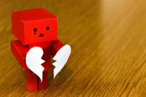 Crying Red Amazon Danbo on Brown Wooden Surface holding brown heart