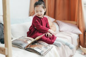 Girl in Red Long Sleeve Dress Sitting on Bed Reading Book with a smile on her face.
