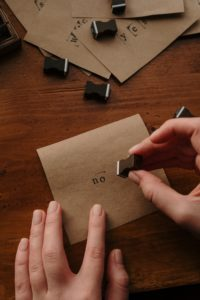 Person Holding Brown Paper and a letter stamp reading