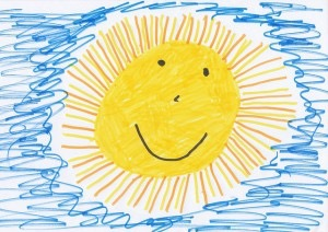 Child drawing of a smiling sun in blue sky
