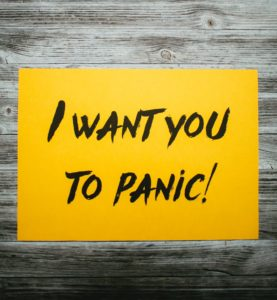 A yellow I want you to panic! sign on wooden background.